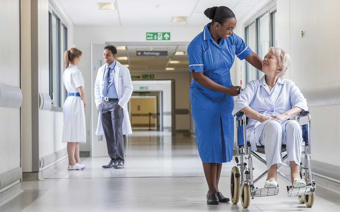 Nurse stood in a hospital corridor whilst speaking to a patient in a wheel chair